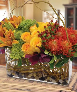 A rectangular modern arrangement full of roses, lilies and hydrangea in autumn hues.