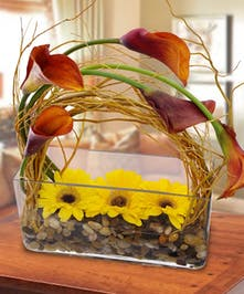 An elegant and modern rectangular vase with mango colored calla lilies and yellow gerbera daisies.