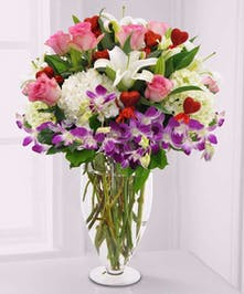 Luxurious gathering of Valentine's flowers designed in a clear glass vase