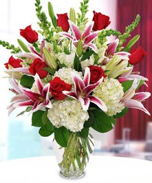 Love is in the air with aromatic Stargazer lilies, vivid red roses, white snapdragons and hydrangea.