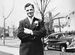 Pictured as a young man, Frank Mancuso Sr. poses in a suit and tie, beside a classic car