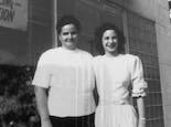 Two of the Mancuso sisters pose in front of the store's picture window in the mid-20th century